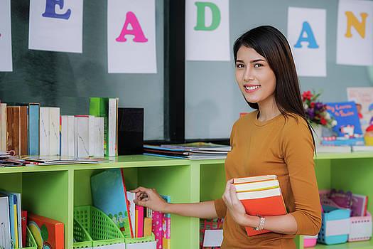 Teacher prepare book for teach student in preschool by Anek Suwannaphoom