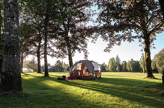 Tent setup for camping in the countryside at sunset by Bradley Hebdon