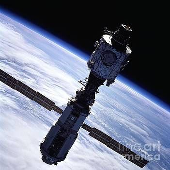 R Muirhead Art - The International Space Station contrasted against cloud covered home planet and darkness of space
