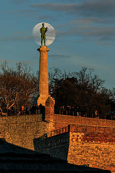 The Moon Rising Behind the Victor Statue in Belgrade in the Golden Hour by Dejan Kostic