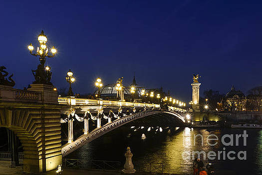The Pont Alexandre III, arch bridge in Paris at night, Grand Palais behind, France. by Perry Van Munster