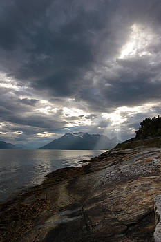 The sun is shining through storm clouds over Salangen-Fjord by Intensivelight