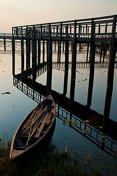 The wood reflex bridge on lotus pond by Nichapa Sornprakaysang