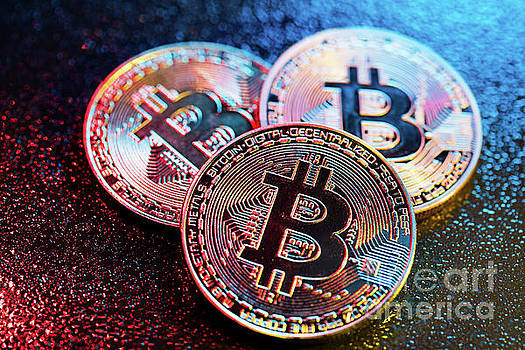 Michal Bednarek - Three bitcoin coins in a colorful lighting.