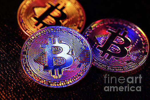 Michal Bednarek - Three coins with bitcoin logo laying on a black background