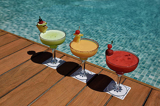 Reimar Gaertner - Three colorful alcoholic drinks on a deck next to a pool