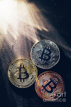 Michal Bednarek - Three colorful bitcoin coins and beams of light.