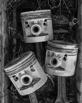 Three Pistons In A Pan Close Up by Paul DeRocker