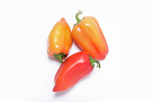 Three Sweet Peppers On A White Background by Sergei Dolgov