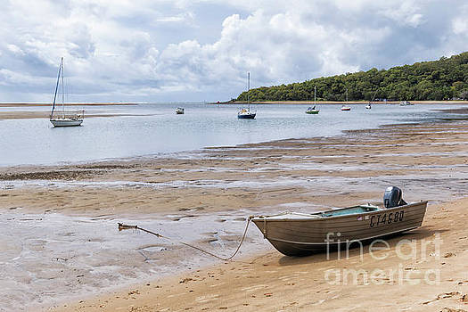 Tinnie dinghy on beach shore at low tide at 1770 by Carl Chapman