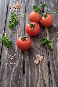Tomatoes parsley and salt on wooden background by Julian Popov