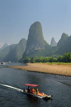 Reimar Gaertner - Tour boat raft traveling down the Li river Guangxi China with ta