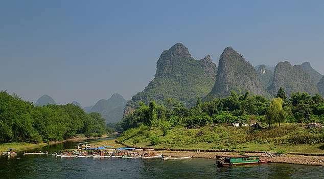 Reimar Gaertner - Tour boat rafts on the shore of the Li river Guangxi China with