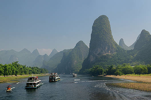 Reimar Gaertner - Tour boats traveling down the Li river Guangxi China with tall k