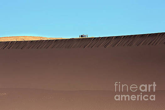 Tourists stand on top of a sand dune in Valle de la Luna by Louise Heusinkveld