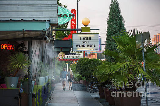 Herronstock Prints - Tourists stroll past the iconic neon signs of South Congress Avenue, a local favorite hip and eclectic neighborhood