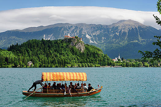 Traditional Pletna boat with colorful canopy on Lake Bled with B by Reimar Gaertner