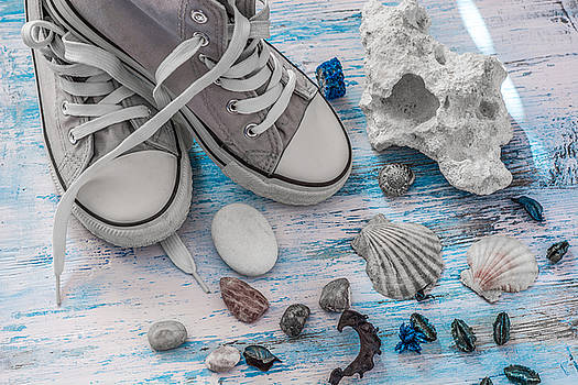 Travel stll life with sneakers and stones on wooden board by Julian Popov