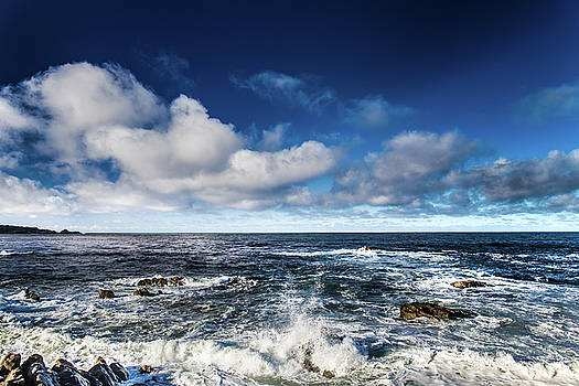 Turquoise Pacific ocean sea water rolling waves and rock with bl by Jingjits Photography