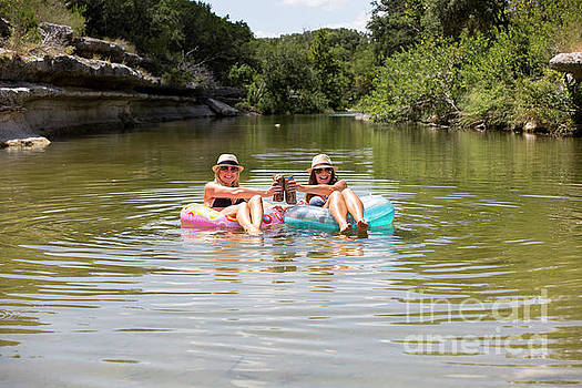 Herronstock Prints - Two attractive females beat the summer heat by drinking a cold beer and relaxing in Bull Creek Greenbelt swimming hole