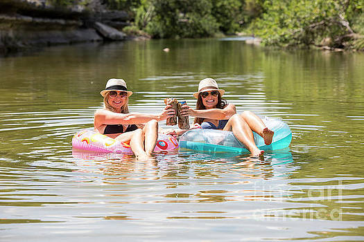 Herronstock Prints - Two attractive females relax with a cold beer at a swimming hole in the Bull Creek Greenbelt in west Austin