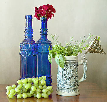 Two blue bottles, grapes and herbs by Luisa Vallon Fumi