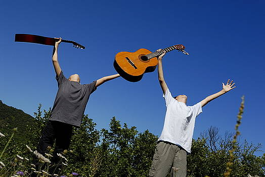 Sami Sarkis - Two boys standing in meadow holding guitars in outstretched arms