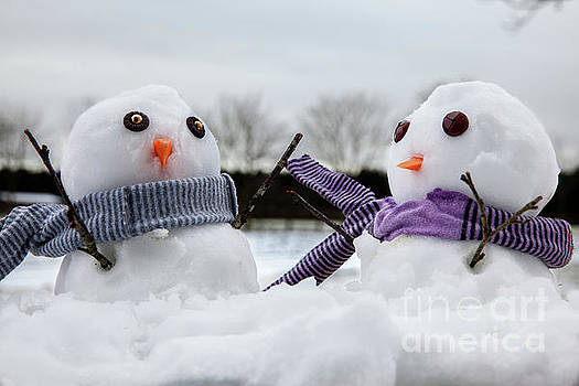 Two cute snowmen wearing scarfs and twigs for arms by Simon Bratt Photography LRPS