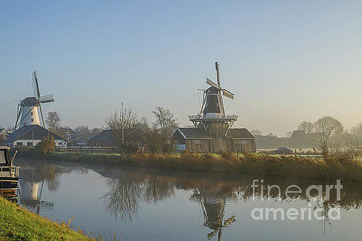 Two dutch windmills in the fog by Patricia Hofmeester