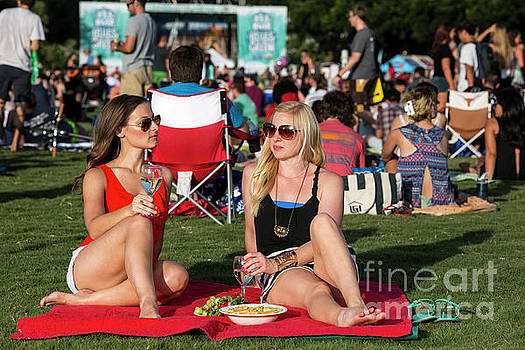 Herronstock Prints - Two fit attractive women sit on a blanket drinking wine at the Blues On The Green