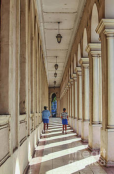 Patricia Hofmeester - Two girls walking in an arched hallway