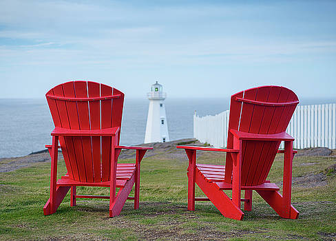 Two Red Adirondack Chairs looking out to a Lighthouse by Art Whitton