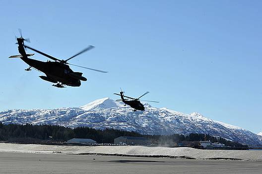 Two US Army Black Hawk Helicopters launch towards villages on Kodiak Island by Paul Fearn