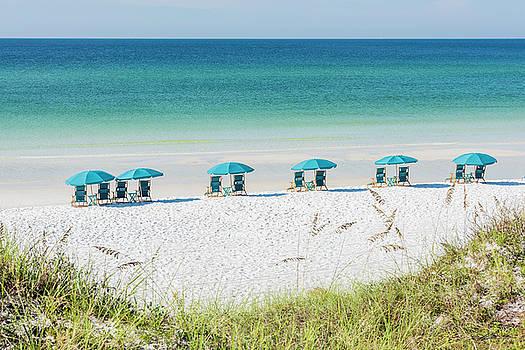 Umbrellas Await On The Beach by Kurt Lischka