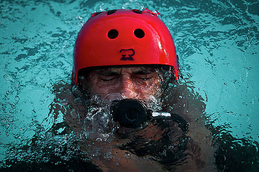 US Marine Corps platoon commander practises using an emergency breathing system at base pool Hawaii by Paul Fearn