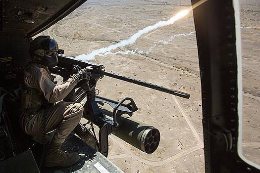 US Marine fires a GAU21 50 Caliber machine gun out a door by Paul Fearn