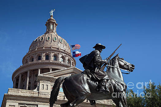 Herronstock Prints - USA and Texas Flags fly next to the Texas Ranger statue at the Texas State Capitol