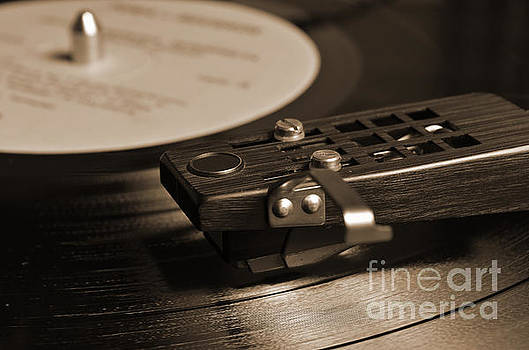 Angelo DeVal - Vinyl record playing on a turntable in Sepia