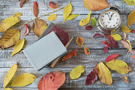 Vntage books and clock on wooden table. Autumn composition. by Julian Popov