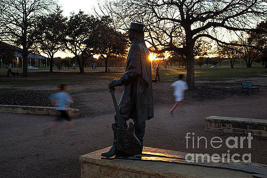 Herronstock Prints - Walkers runners and joggers pass by the Stevie Ray Vaughan Memorial Statue most popular attraction