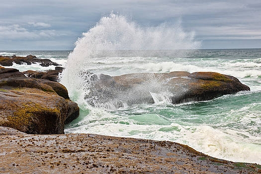 Waves crash at high tide against the basalt rocks at Yachats. by Larry Geddis