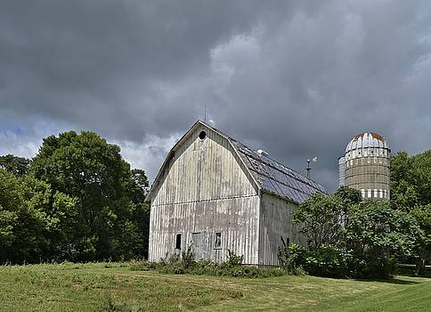 Weathered Barn and Silo under a cloudy sky by Steven Liveoak
