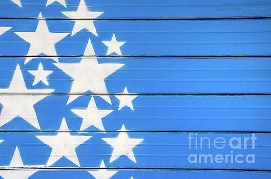White Stars On Blue Background Painted On A Closed Shutter by Luca Lorenzelli