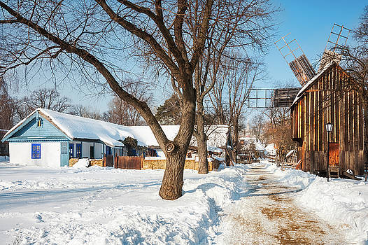 Windmill and an old cottage covered in snow at the Village Museum, Bucharest by Daniela Constantinescu