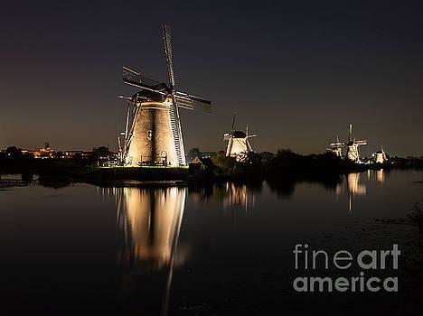 Windmills illuminated at night by IPics Photography