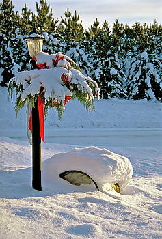 Winter lamp post in the snow with Christmas bough by Peter Pauer
