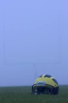 Wolverine helmet on the field in heavy fog by Michigan Helmet