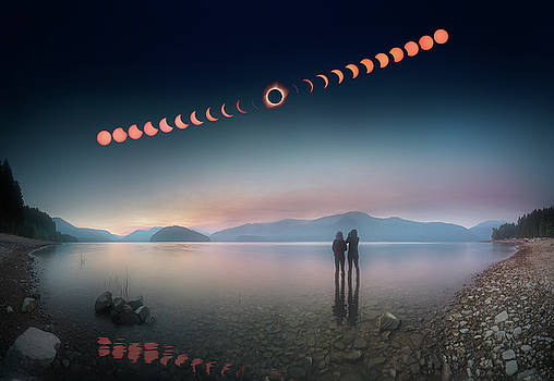 Woman and girl standing in lake watching solar eclipse by William Lee