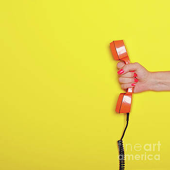 Woman hand holding retro orange phone tube against yellow backgr by Aleksandar Mijatovic