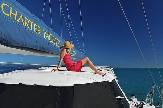 Woman in red dress on sailing catamaran in the Whitsundays by Keiran Lusk